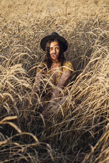 Portrait of young woman wearing hat sitting in corn field