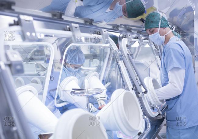 Scientists processing human tissue in insulator laboratory