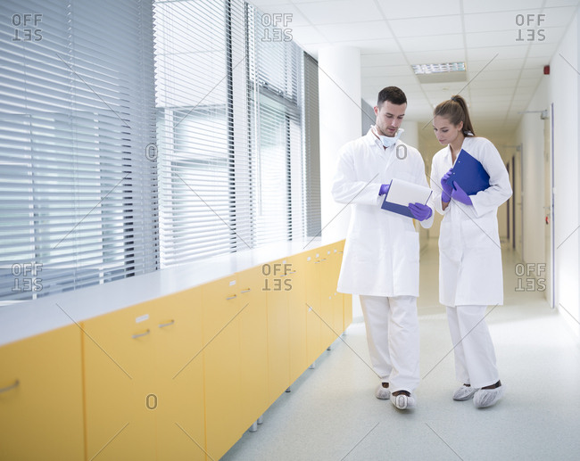 Man and woman in lab coats discussing on hallway