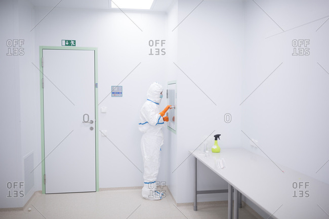 Lab technician wearing cleanroom overall at material sluice