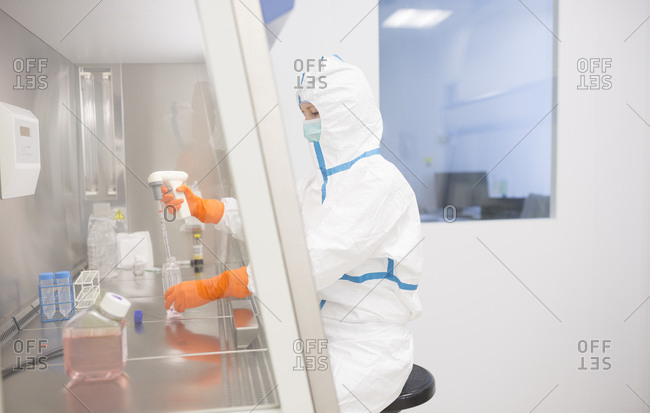 Lab technician wearing cleanroom overall  working in sterile laminar box