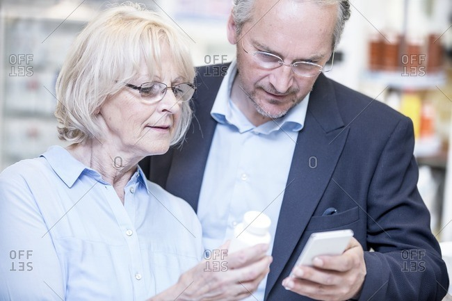 Senior couple checking medicine on mobile phone in pharmacy.