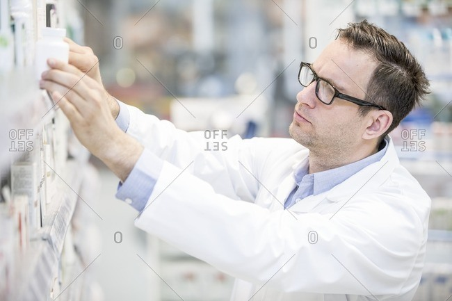 Male pharmacist looking for medicine on shelf in pharmacy.
