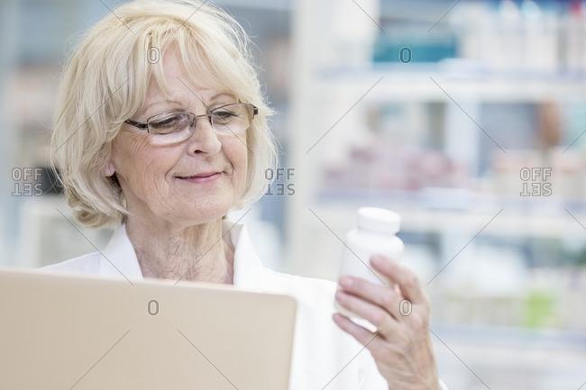 Senior female pharmacist holding laptop and reading label on pill bottle in pharmacy.