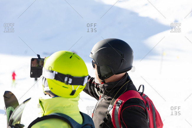 Senior skiers taking selfie with smartphone in ski gear
