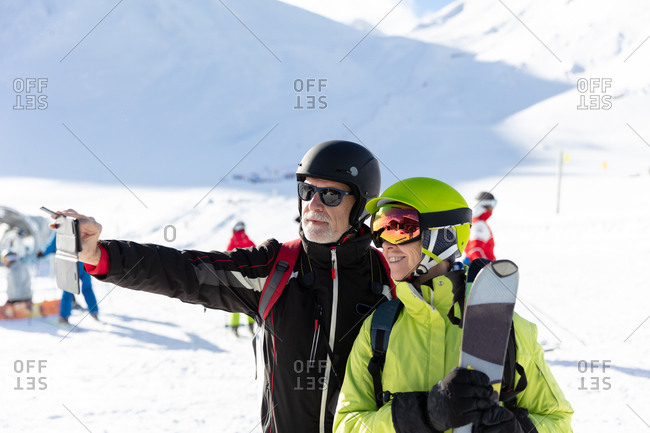 Senior skiers take selfie with mobile phone at ski resort