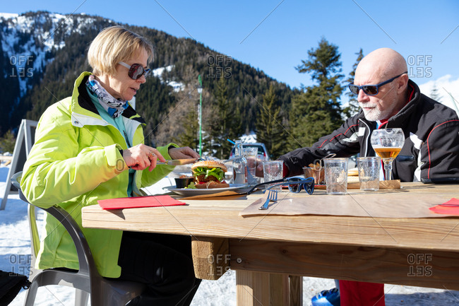 Senior couple eating lunch outdoors at ski resort