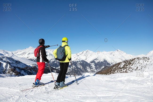 Man and woman with skis in ski resort
