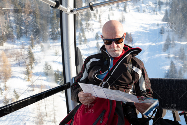 Senior man travelling in ski lift reading map