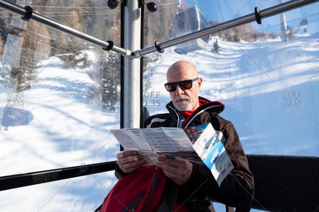 Senior man travelling in ski lift reading ski resort map