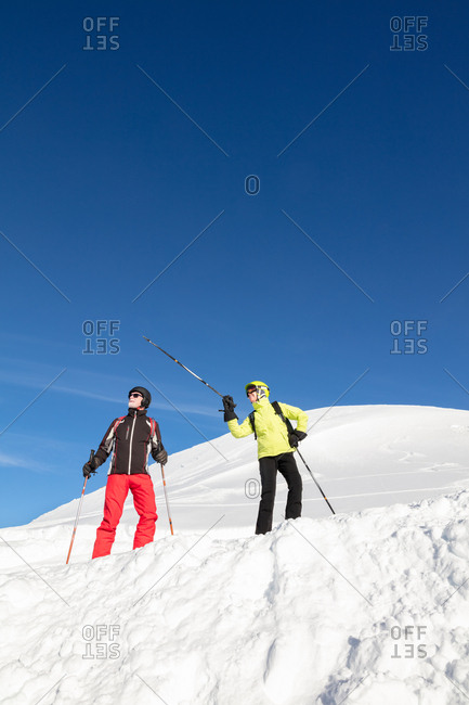 Skiing couple on slope pointing at mountain