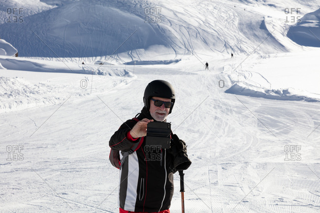 Older man taking selfie on the ski slope