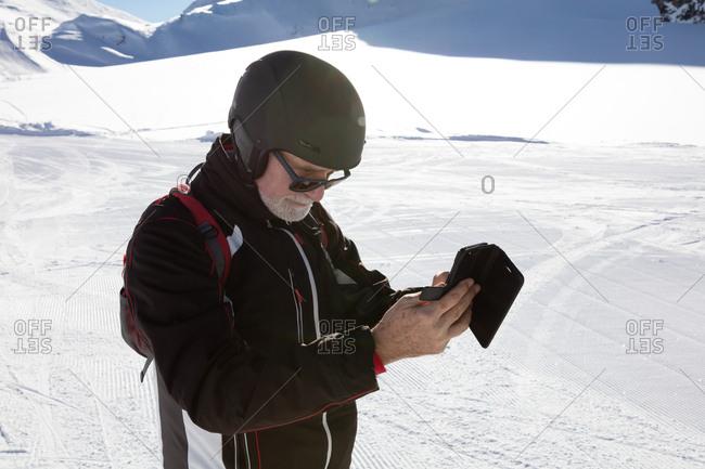 Senior man checking smartphone on ski piste