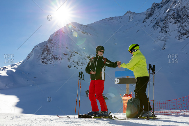 Two senior skiers in winter landscape having a break