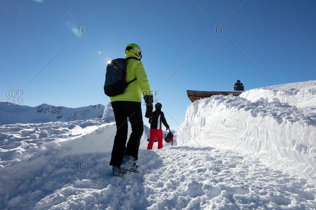 Man and woman in ski gear walking towards ski bar
