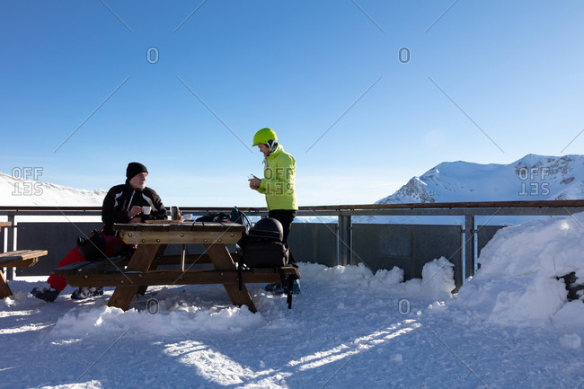 Man and woman taking lunch break with refreshments at table in the mountains