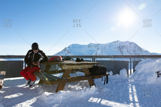 Senior man watching phone at picknick table in ski bar