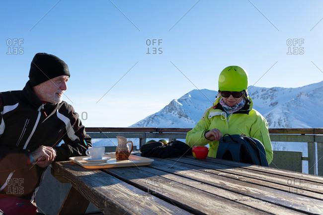 Senior couple interacting while having refreshment at winter bar