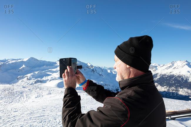 Older man taking photos of mountain range at ski resort