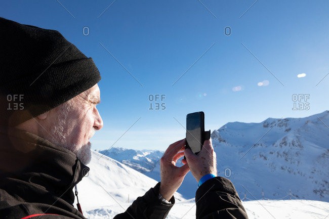 Senior man taking picture of mountain view with mobile phone
