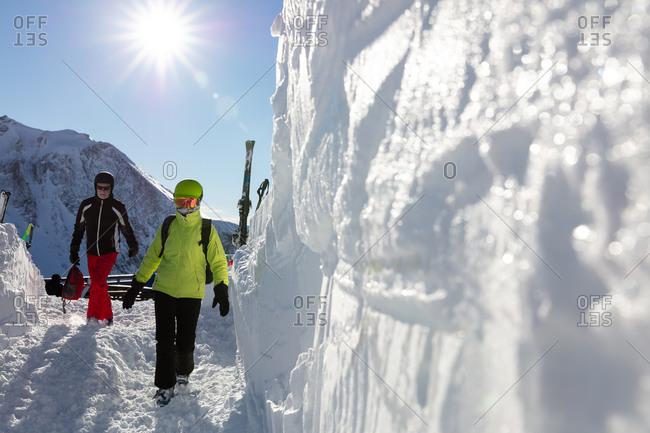 Senior couple in ski gear walking towards ski bar on sunny day