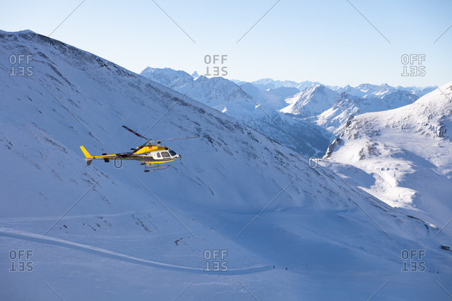 Helicopter flying above scenery with majestic mountains