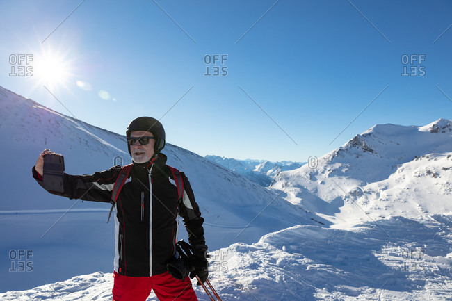A skier uses his smart phone to take a picture