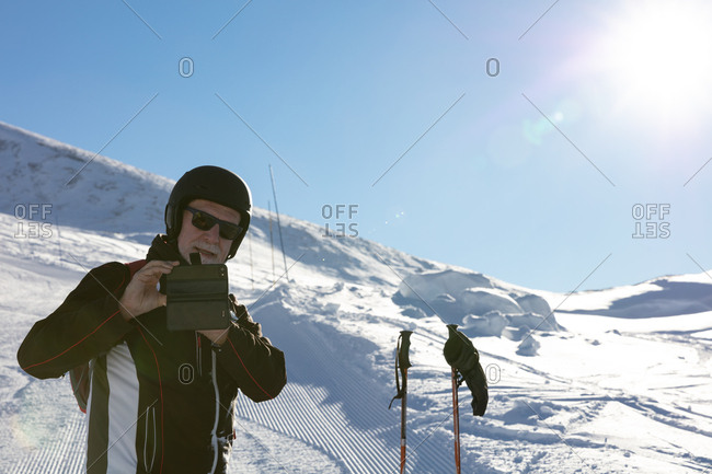 Older man photograping on ski slope with phone