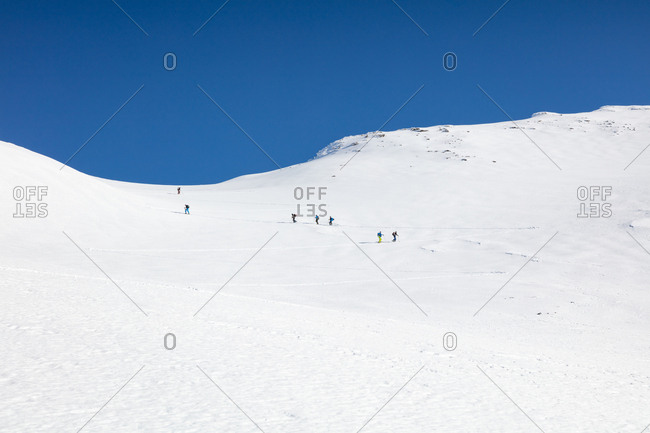 Group of hikers climbing snow capped mountain