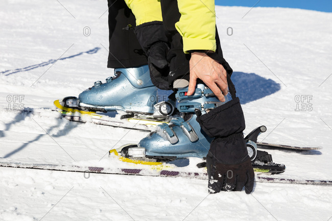 Low section of woman adjusting ski boot on the slopes