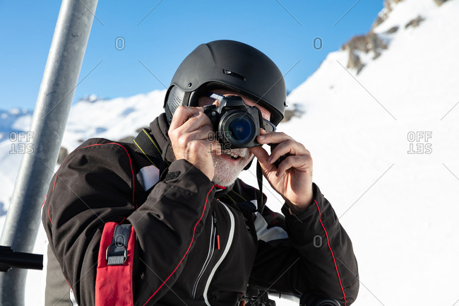 Older man taking creative picture with camera on chair lift at ski resort