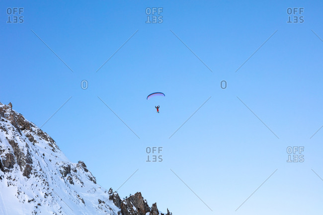 A parapente or paraglider is flying high above the snow capped mountains