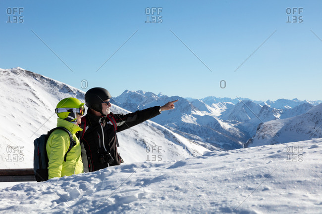 Senior couple on snow covered landscape looking at mountain view