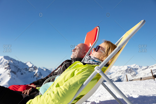 Older couple relaxing in deck chair at ski resort