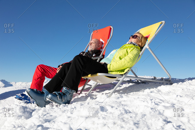 Senior couple  sunbathing in a deckchair near a snowy ski slope