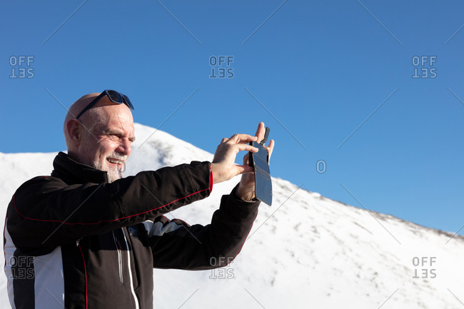 Senior man taking a picture of the view during winter holiday