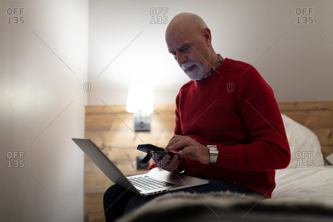 Older man using mobile phone while working on laptop in hotel