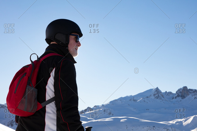 Older man in ski outfit looking at mountains