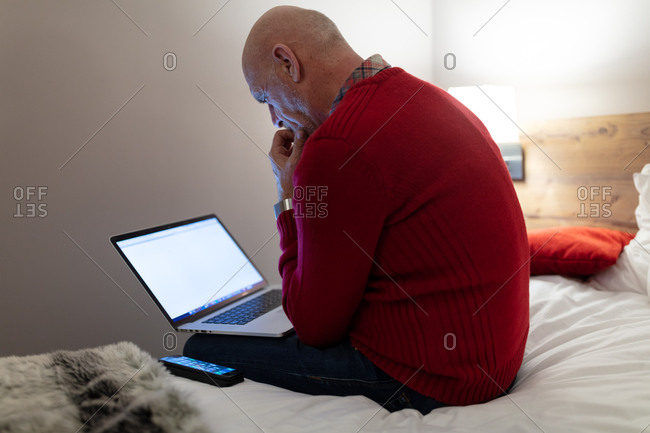 Mature businessman sitting on bed using laptop and phone in hotel room