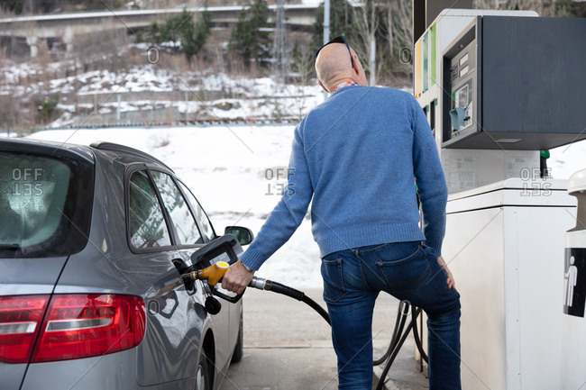 A man fills his car with gas whilst looking at the meter