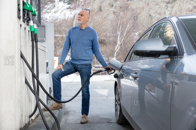 A senior man fills his car with gas