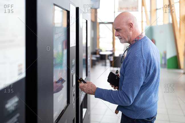 Senior man paying contactless on a vending machine