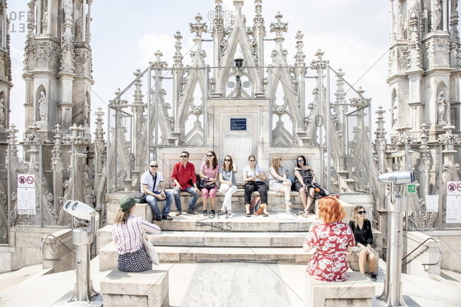 Milan, Italy - May 11, 2018: Tourists sitting on the steps of the duomo terraces at the Milan Cathedral