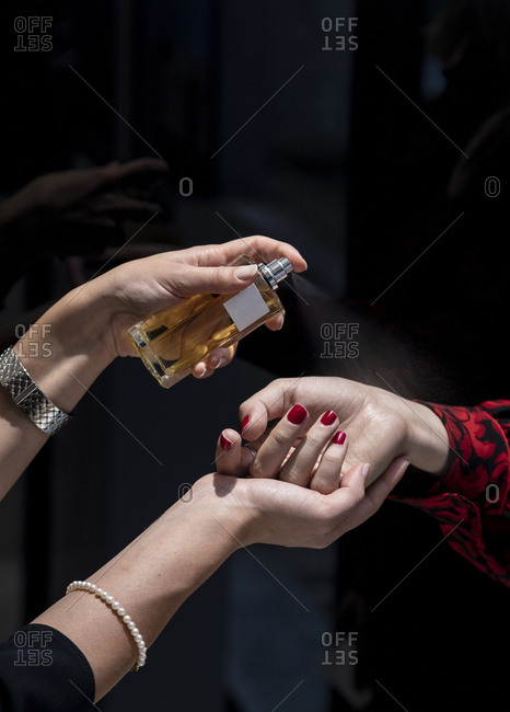Close up of woman testing perfume on her wrist