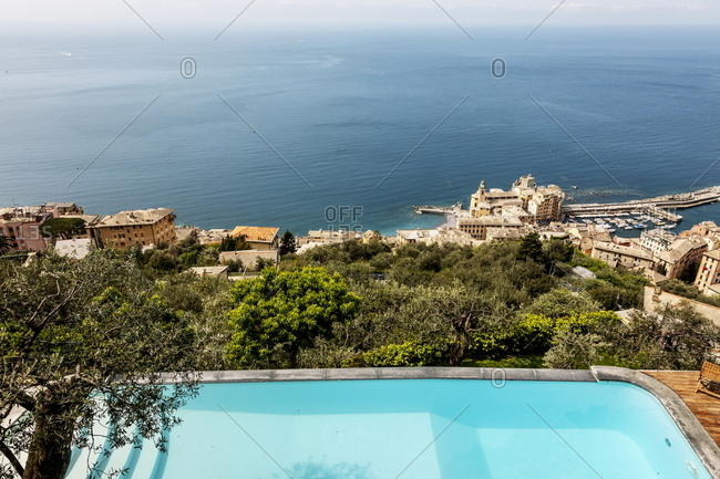 Swimming pool on coastal bluff overlooking Italian village by the sea