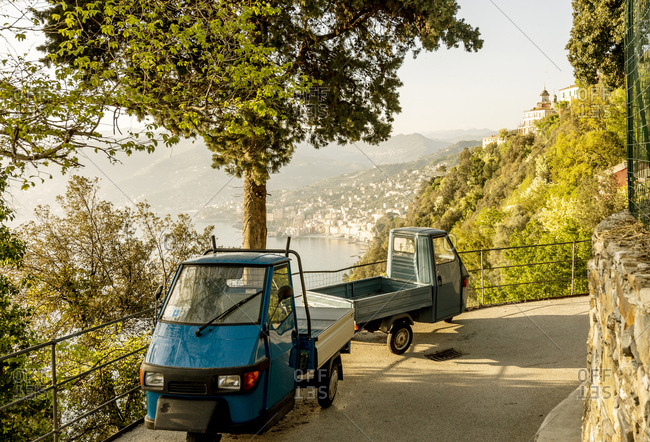 San Rocco di Camogli, Italy - April 24, 2018: Piaggio ape vehicles parked along road overlooking Italian coastal village