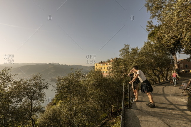 San Rocco di Camogli, Italy - April 24, 2018: Tourists leaning against railing at scenic overlook on the Italian coast