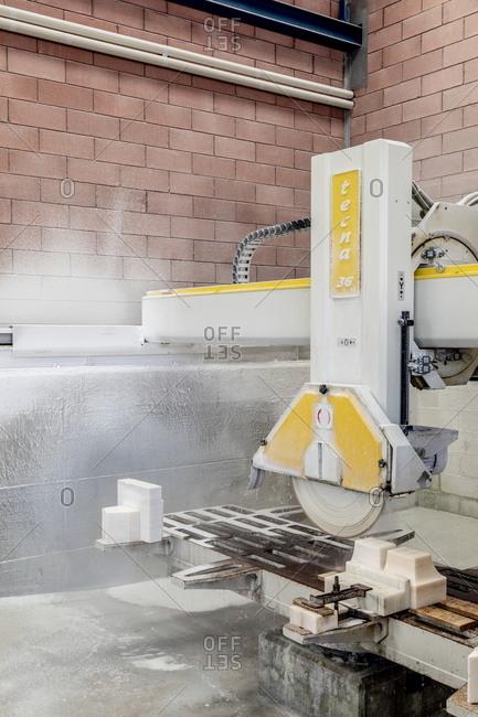 Milan, Italy - May 11, 2018: Industrial power saw cutting marble for restoration at La Veneranda Fabbrica del Duomo