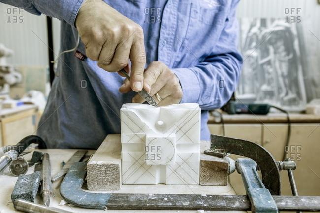 Milan, Italy - May 11, 2018: Artisan restoring a historic marble piece from the Milan Cathedral at La Veneranda Fabbrica del Duomo