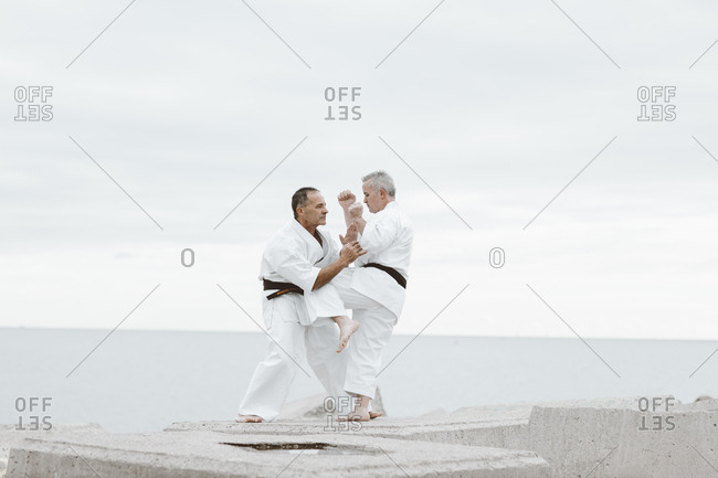 Karate fighters practicing martial arts on rocks by the ocean